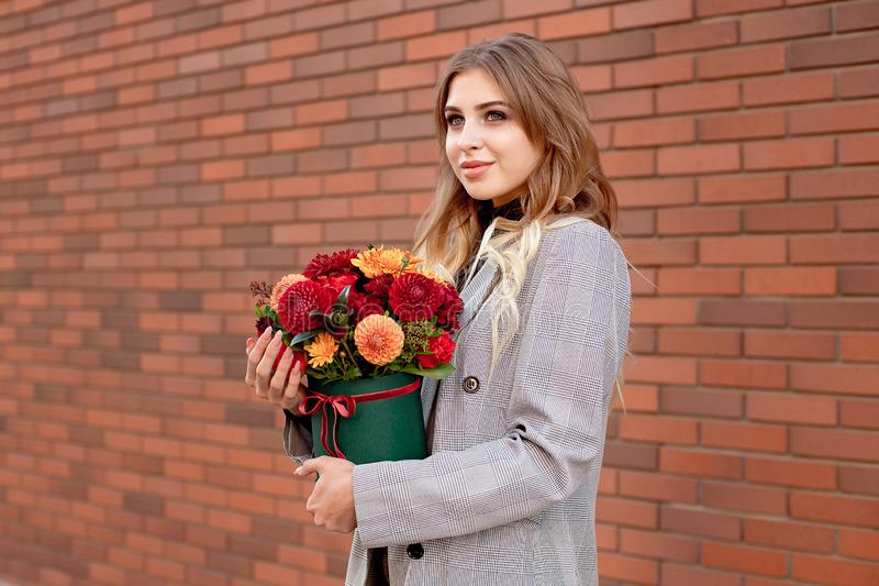 Caucasian woman standing on the street near storefront shop windows holding flower-box with happy smile. Caucasian woman standing on the street near storefront royalty free stock photography