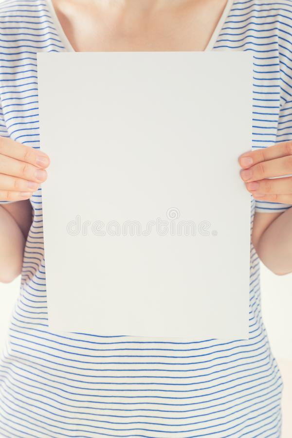 Caucasian woman in striped t-shirt hold a white blank paper sheet in hands royalty free stock photos