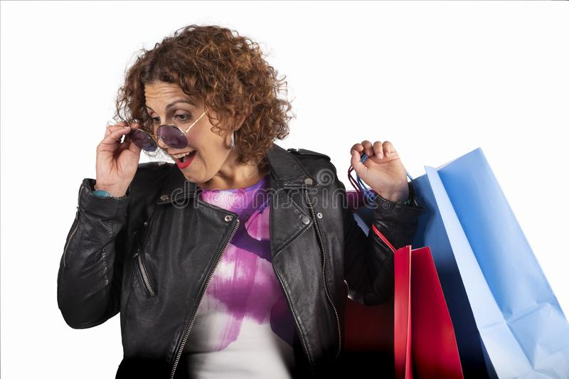 Caucasian woman with sunglasses looking down surprised, with shopping bags on white background stock photo
