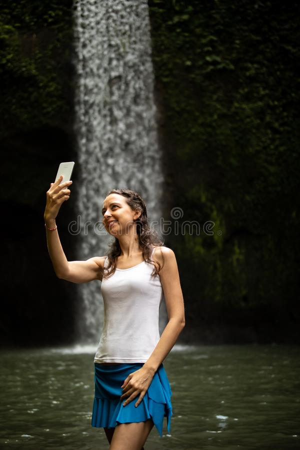 Caucasian woman taking selfie with smartphone and enjoying waterfall landscape. Happy Caucasian woman enjoying waterfall landscape in tropic, taking selfie with stock image