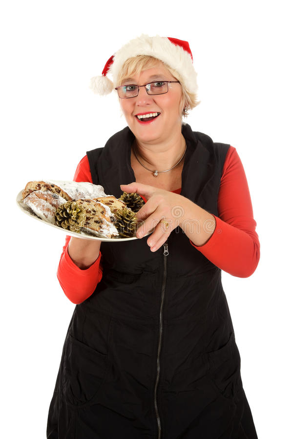 Caucasian woman, traditional Christmas cake. Attractive middle aged caucasian woman with Santa hat taking a piece of traditional German Christmas cake. Studio royalty free stock photos