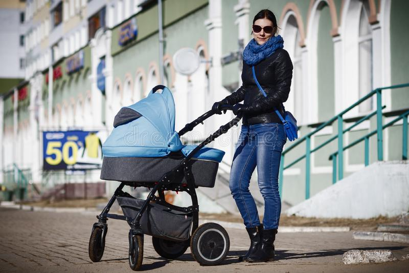 Caucasian woman walking in the park with her son in the baby carriage royalty free stock images