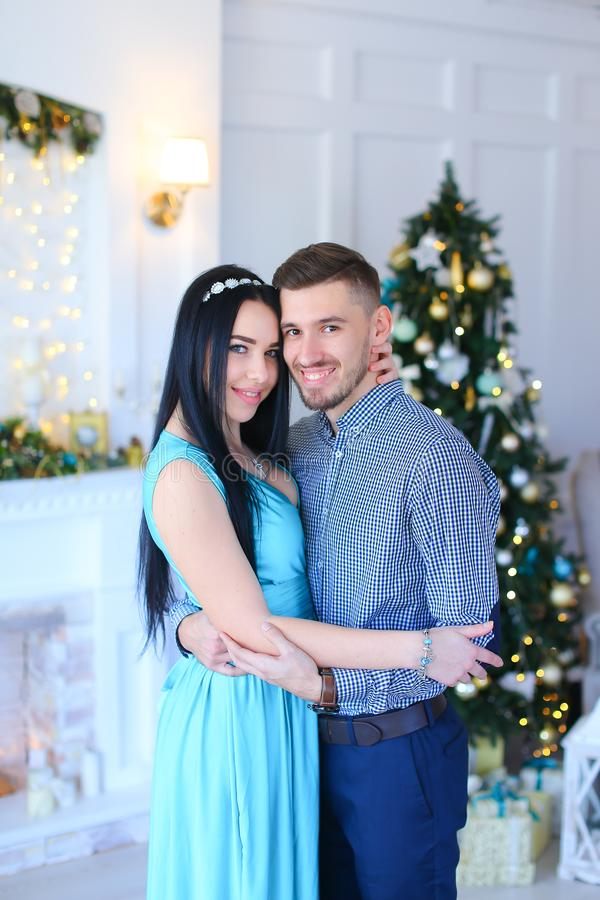 Caucasian woman wearing dress standing with husband near fireplace and Christmas tree. stock image