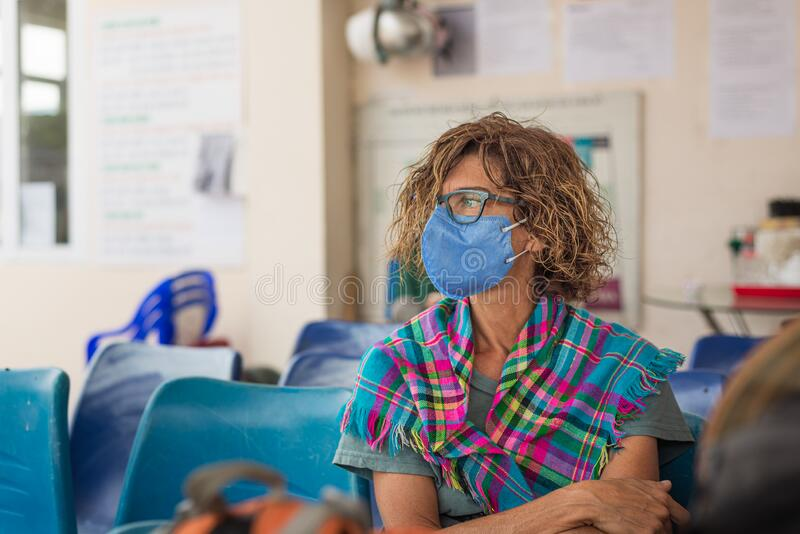 Caucasian woman wearing sanitary mask indoors while traveling in Vietnam. Tourist in waiting room with medical mask protection royalty free stock photo