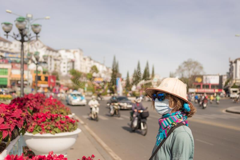 Caucasian woman wearing sanitary mask outdoors in Da Lat city centre Vietnam. Tourist with medical mask protection against risk of royalty free stock images
