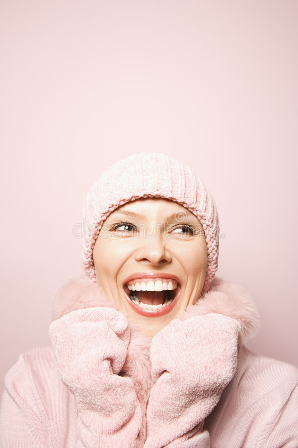 Caucasian woman wearing winter coat and hat. Smiling Caucasian mid-adult woman on pink background wearing winter coat and hat royalty free stock image