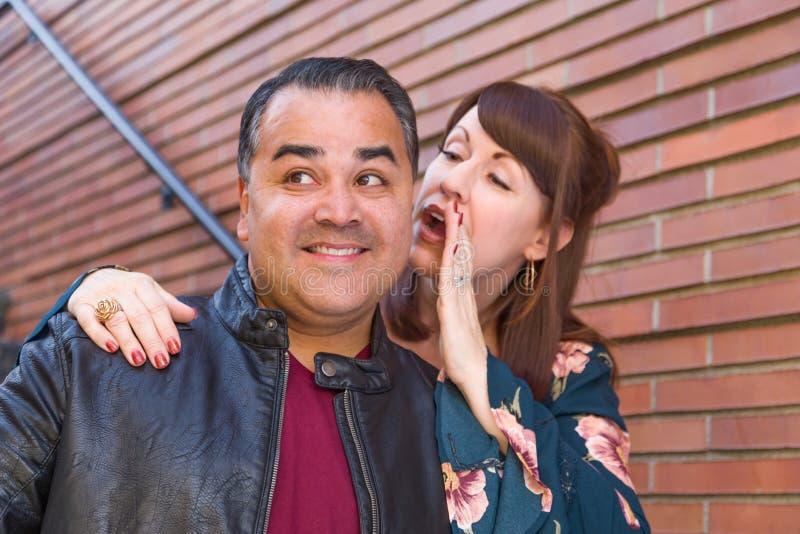 Caucasian Woman Whispering Secret in Hispanic Man`s Ear royalty free stock image