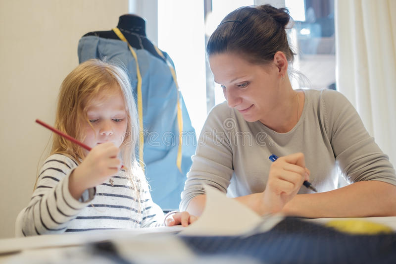 Caucasian woman working while her daughter drawing picture near her royalty free stock photo