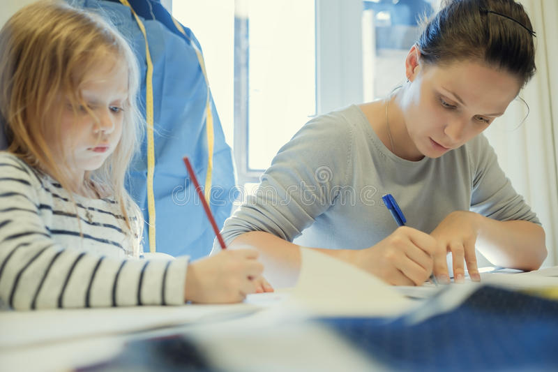 Caucasian woman working while her daughter drawing picture near her stock photography