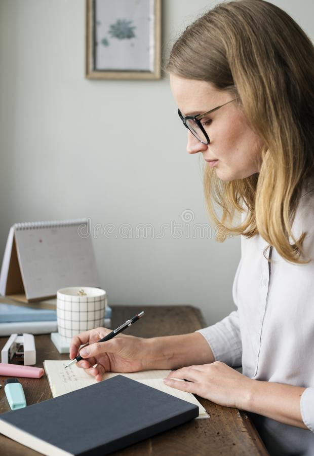 Caucasian woman writing a note royalty free stock photo