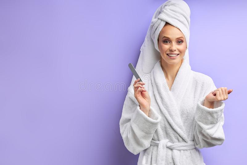 Caucasian women in bathrobe look at camera while trimming nails with nailfile royalty free stock image
