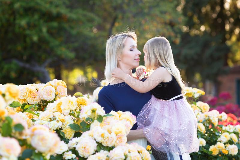 Caucasian woman with little girl in hands in rose garden, mommy and me concept, cuddling, looking to each other royalty free stock image
