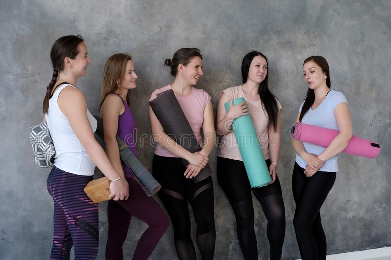 Women stand near wall with rubber mats in hands, have fun waiting for yoga class. Caucasian women stand near wall with rubber mats in hands, have fun waiting for royalty free stock images
