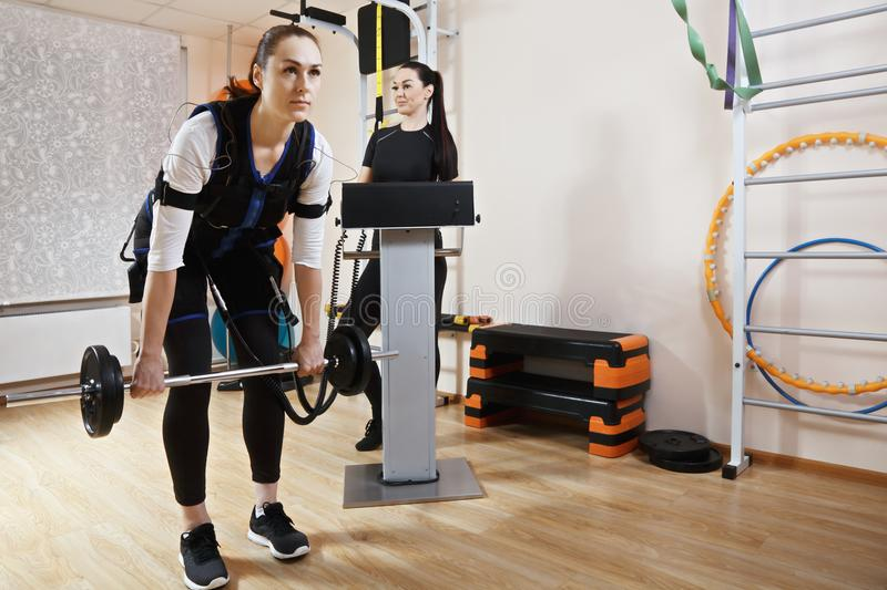 Training with weight. Caucasian women training with weight in gym. Female coach standing aside manages electric muscle stimulation purposed to increase stock photography