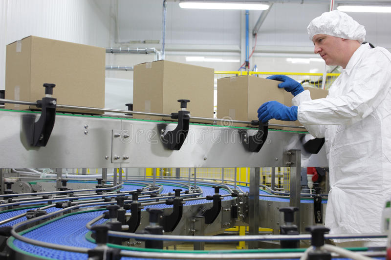 worker in white apron at packing line stock images