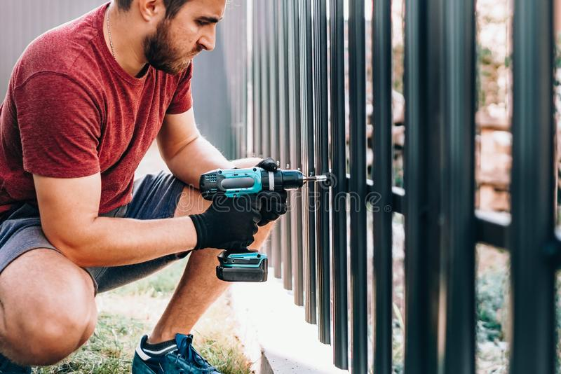 caucasian worker working with an electric screwdriver on the construction site stock image
