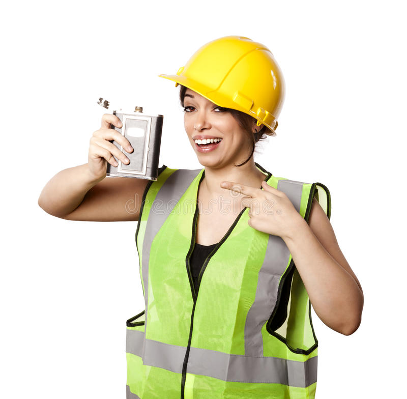 Alcohol Safety Woman. Caucasian young adult woman in her mid 20's wearing reflective yellow safety helmet and safety vest, holding a hip flask while pointing at royalty free stock photos