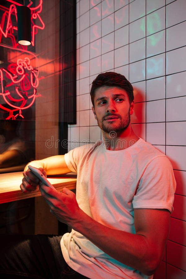 Caucasian young attractive serious man sitting in cafe stock photos
