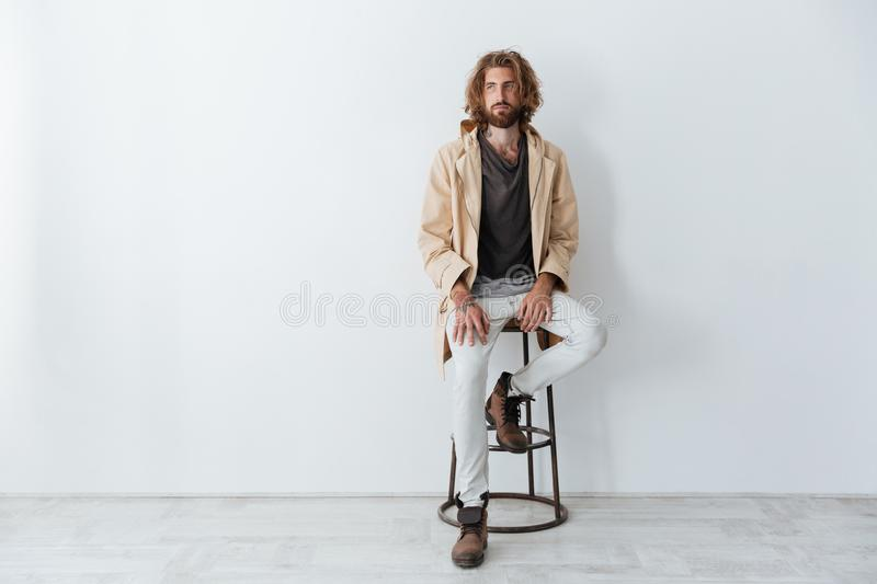 Caucasian young bearded man sitting isolated over grey wall royalty free stock images