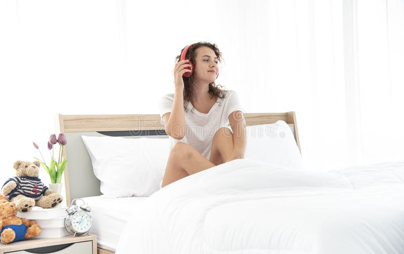 Caucasian young and beautiful and happiness woman sitting on the  comfortable double bed in the modern or minimal royalty free stock image