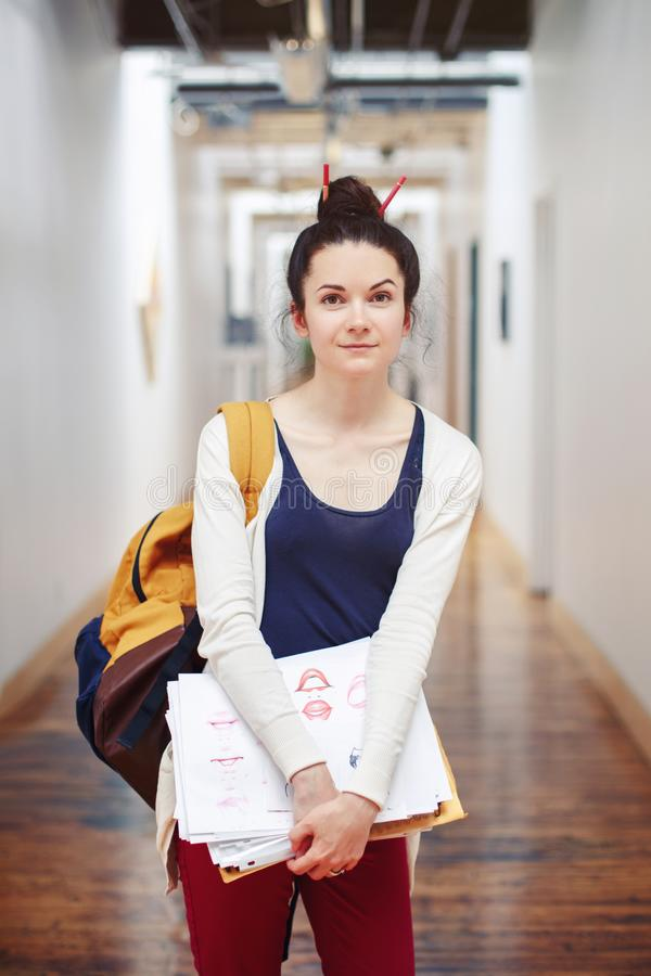 Caucasian young brunette woman student female drawing designer artist in hall of college university. Portrait of beautiful white Caucasian young brunette woman stock photography