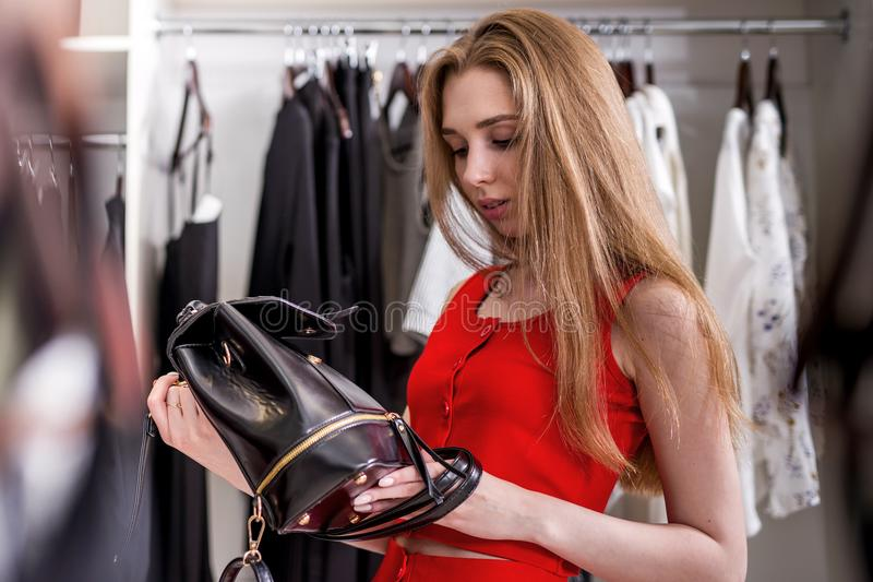 Caucasian young female shopper choosing leather backpack from new women s collection. Caucasian young female shopper choosing leather backpack from new woman s stock images