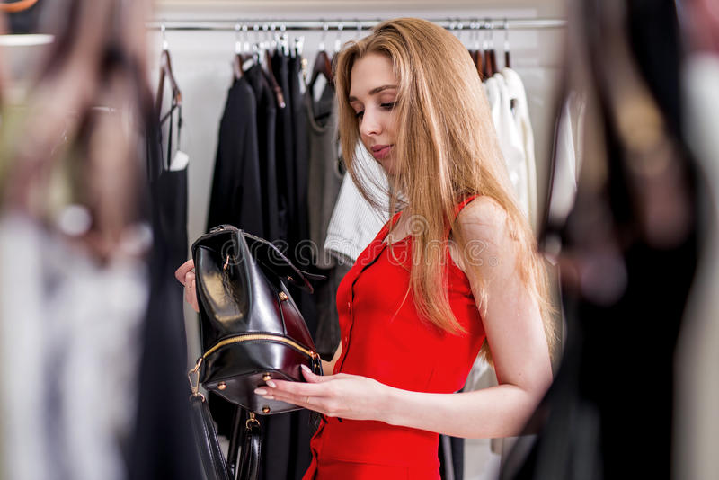 Caucasian young female shopper choosing leather backpack from new women s collection. Caucasian young female shopper choosing leather backpack from new woman s stock photography