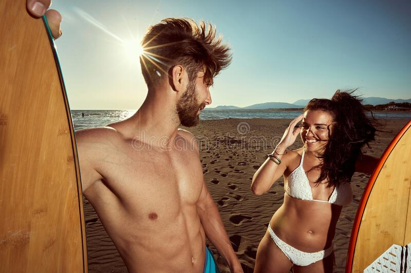 Caucasian  fit, sexy couple, talking on a beach, holding surfboards. ultraviolet radiation, protection concept royalty free stock photo