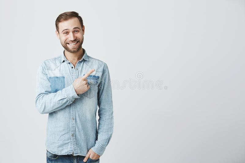 Caucasian young male in denim shirt grins at camera, indicates at copy space, advertises something. Happy bearded man royalty free stock image