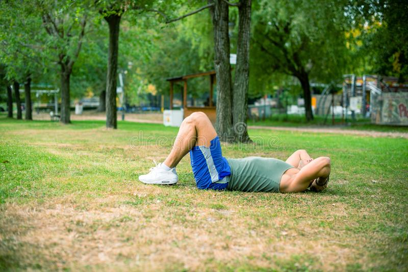 Man exercising in park stock photos