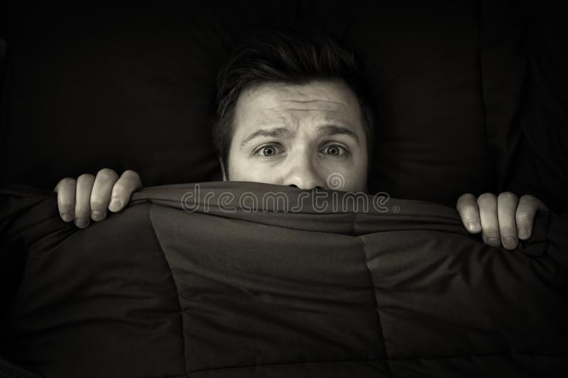 Caucasian young man hiding in bed under the blanket at home. royalty free stock photos