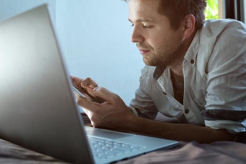 Caucasian young man lying on bed at his laptop. Working at home. royalty free stock photo