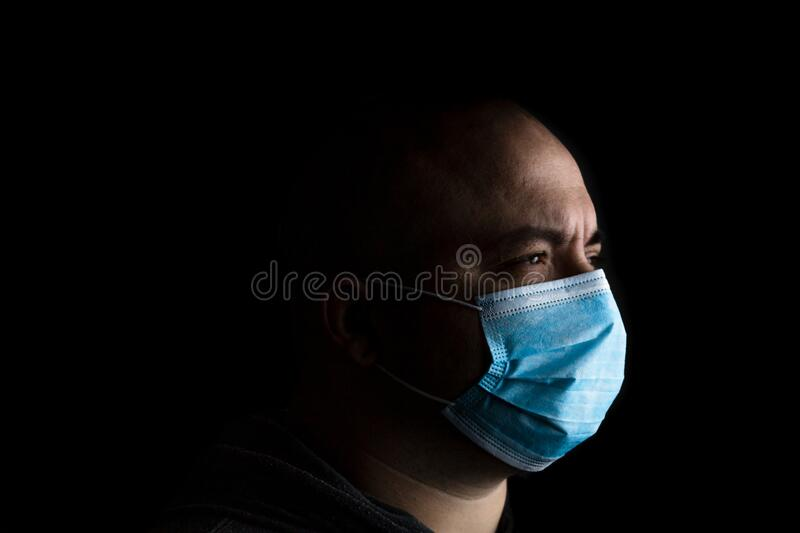 Caucasian young man with medical protective face mask illustrates pandemic coronavirus, Covid 19 disease isolated on black copy. Space. Covid-19 outbreak, flu royalty free stock photos