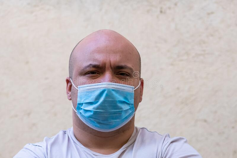 Caucasian young man with medical protective face mask illustrates pandemic coronavirus, Covid 19 disease isolated, copy space. Covid-19 outbreak, flu stock images