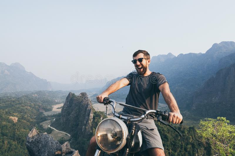 Caucasian young man riding motorcycle on top of the mountains in Vang Vieng, Laos royalty free stock photography