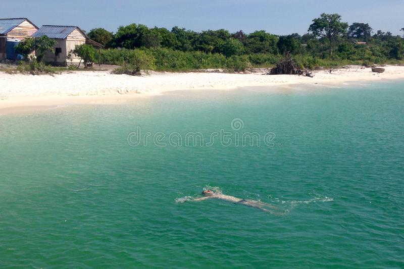 Caucasian young man swims on his back towards the shore in the sea. White sand, beach hut and green sea on a sunny day. Top view.  royalty free stock images