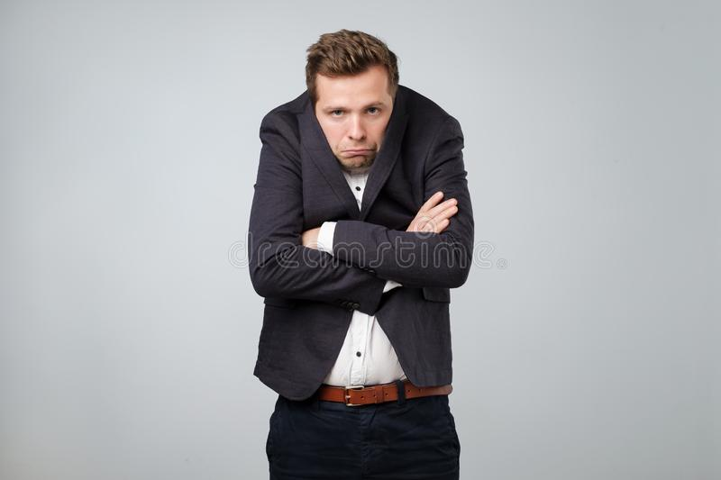 Caucasian young man in too big suit. He is offended and looking stressed. Looking silly in a suit of wrong size royalty free stock photo