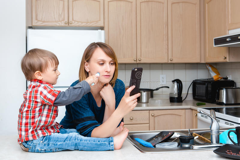 Caucasian young woman mother housewife taking pictures selfie in kitchen, her child son boy playing and drawing on her cheek stock images
