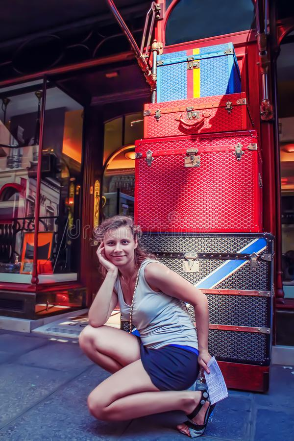 Caucasian young woman near luxury hotel with lots of luggage. Many suitcases of modern rich woman. Girl with large pile of suitcases stacked one on one stock images