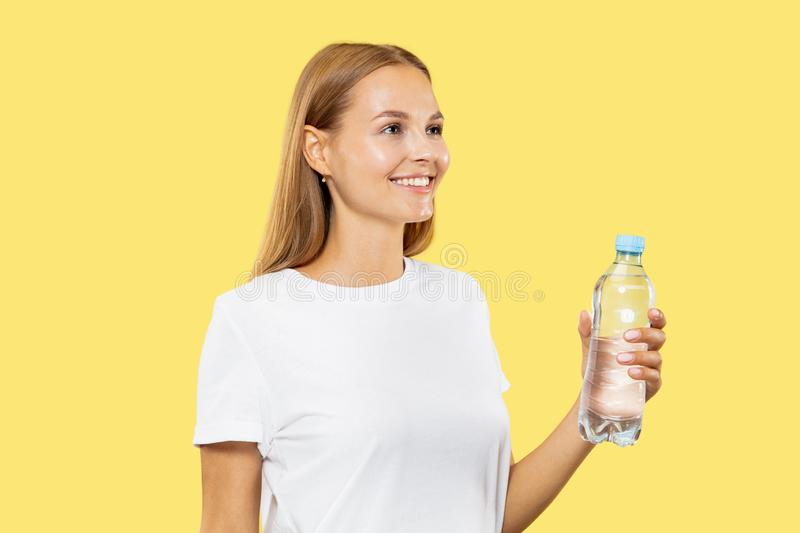 Caucasian young woman`s half-length portrait on yellow background stock image