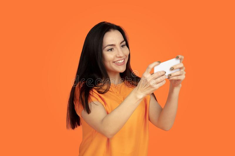 Caucasian young woman`s portrait on orange background. Caucasian young woman`s portrait on orange studio background. Beautiful female brunette model in shirt stock images