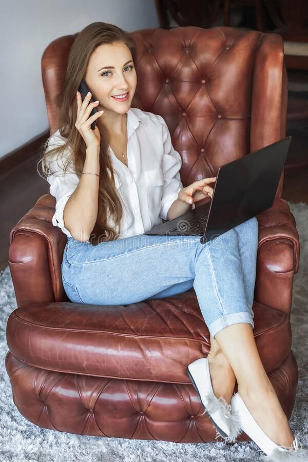 Caucasian young woman working on laptop computer and .calling on mobile phone. Women spending time at home.  royalty free stock image
