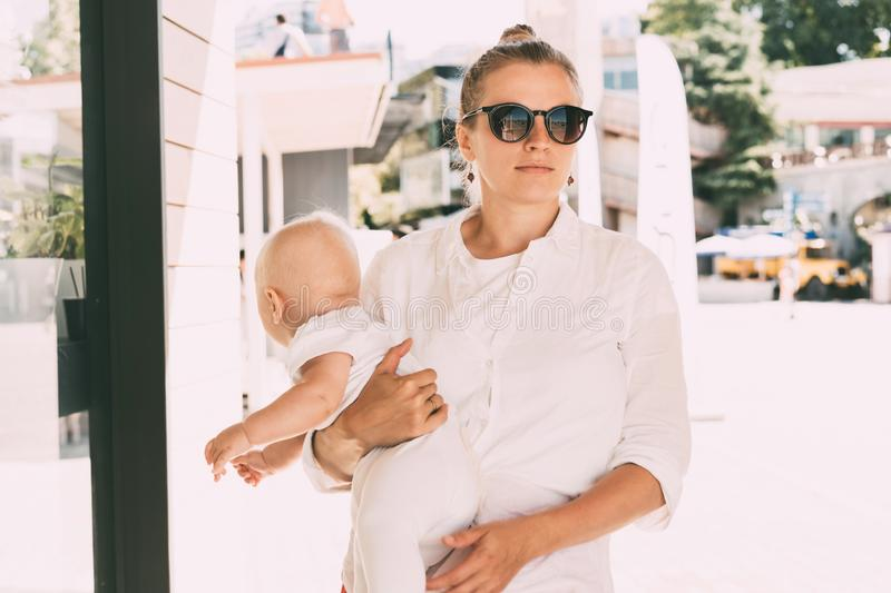 Successful confident woman with a child. Caucasian young women on a summer day in sunglasses in the city holds the baby in her arms. Lifestyle urban portrait of stock images