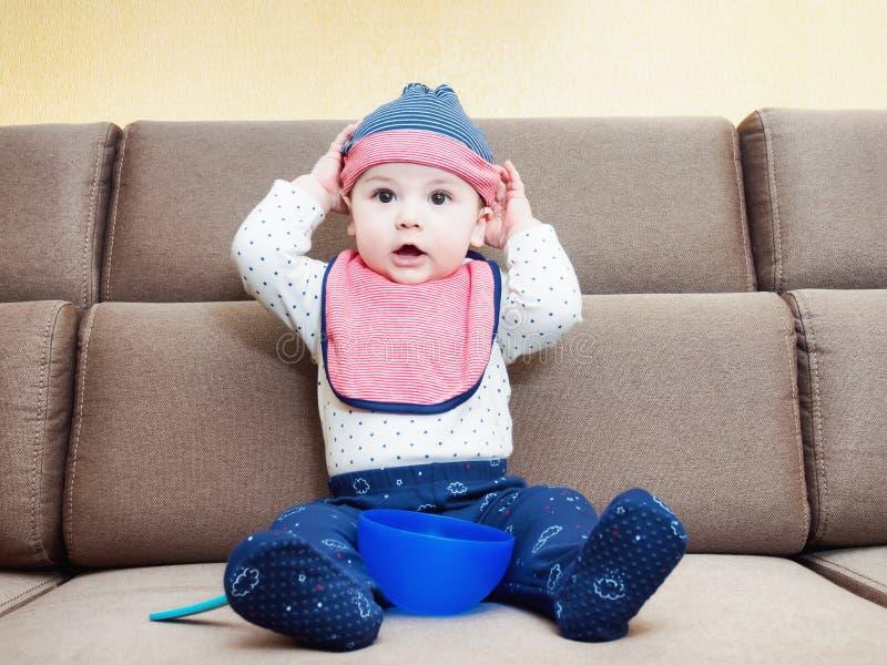 Caucasianen behandla som ett barn weared haklappsammanträde för pojke på soffan hemma arkivfoton