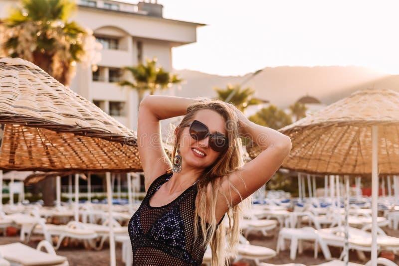 Caucasianen garvade att le den unga kvinnan i solglasögon på stranden i det contra solljuset royaltyfri foto