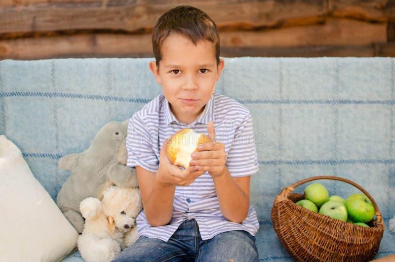 Caucasiano de nove anos senta-se num baloiço de jardim e come maçãs verdes Feliz filho sorridente, infância descuidada na foto de stock