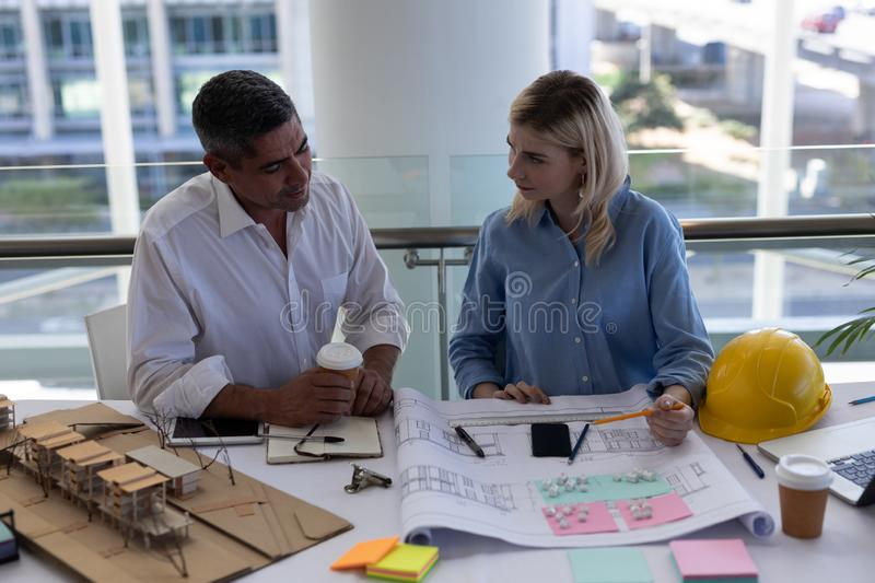 Caucasians architects discussing over blueprint at desk in office. Front view of Caucasians architects discussing over blueprint at desk in modern office royalty free stock photo