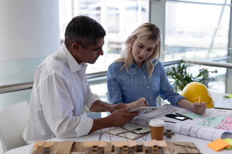 Caucasians architects discussing over blueprint at desk in office. Side view of Caucasians architects discussing over blueprint at desk in modern office stock photos
