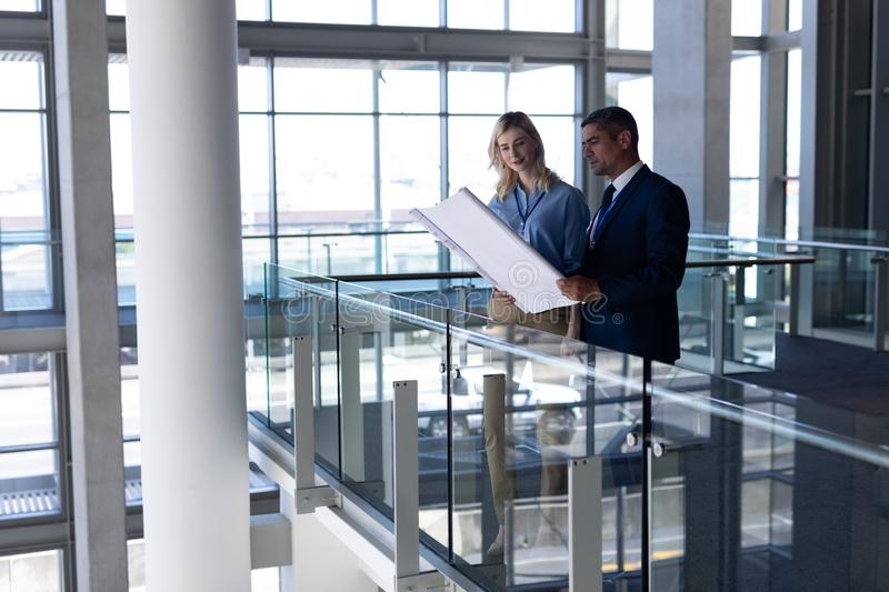 Caucasians architects discussing over blueprint in office. Side view of Caucasians architects discussing over blueprint in modern office royalty free stock photos