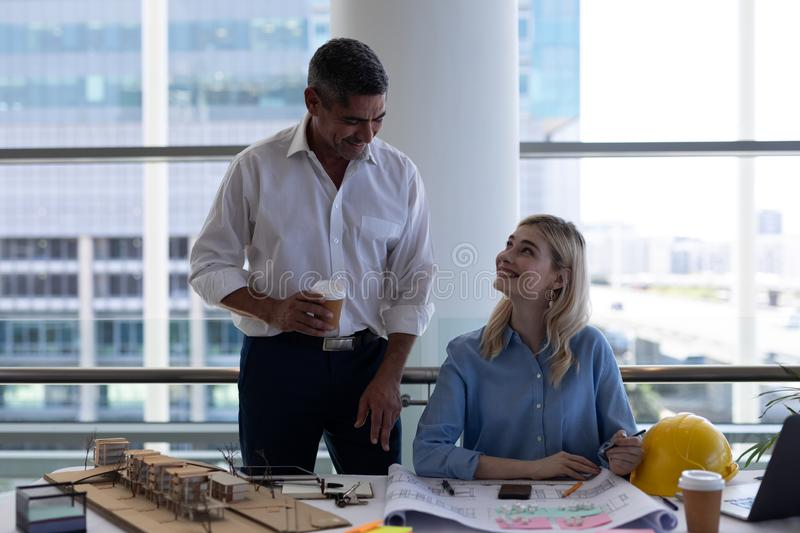 Caucasians architects interacting with each other at desk in office. Front view of happy Caucasians architects interacting with each other at desk in modern stock images